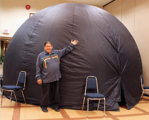 Wilfred Buck posing with his pop up planetarium, photograph courtesy of Manitoba First Nations Education and quoted from Nicole Martillaro's article published 20 march 2019 on cbc.ca.